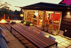 fire pit, table to seat an army, glowing interior, wall of books, cushioned outdoor banquet...i love it all.