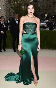 HAILEE STEINFELD in an emerald green gown with a center slit, ab cutouts and a textured bodice, David Webb jewels and a dark lip. Met Gala 2016