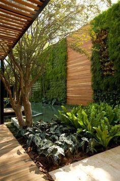 Zelena stena, ki omejuje vrtni prostor pričara sproščenost in ugodje. Kombinacija lesa (podest in stena) daje občutek topline.