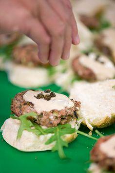 1. Hak de olijven fijn. Pel de ui en het teentje look. Hak beide fijn. Snij de tomaat in plakjes en de citroen in partjes. 2. Laat 1 bokaaltje kappertjes uitlekken en hak ze fijn. 3. Meng het kalfsgehakt met de ui, look, olijven, gehakte kappertjes, citroenrasp en peterselie.