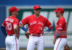 Josh Donaldson #20 of the Toronto Blue Jays and Troy Tulowitzki #2 and Ryan Goins #17 gather in the infield as a call is challenged by video replay in the first inning during MLB game action against the Houston Astros at Rogers Centre on July 9, 2017 in Toronto, Canada.