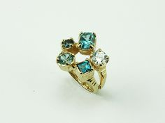 14K Yellow Gold ring with 5 different shapes of Aquamarine gems, by Halllie Katz at Human Arts Gallery in Ojai, CA.  www.humanartsgallery.com