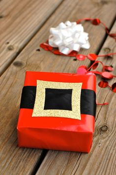 Christmas Gift Wrapping Ideas: Wrap a package in Santa's belt. Cut a square out of glitter paper, then make two slits in it. Slip black ribbon through it and wrap it around red paper.