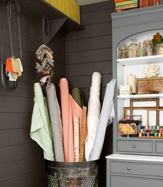 Turn storage into decoration, like stashing bolts of fabric in an industrial trash can and skewering paint swatches on giant safety pins from Ballard Designs.    #storage #houseoftheyear