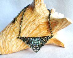 Triangle jewel necklace, bronze filigree triangle surrounds blue glass jewel.