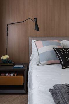 Decoração de apartamento moderno e cinza. No quarto de casal revestimento de madeira, cabeceira cinza., vasos com flores e livros.