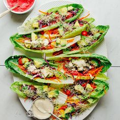 "Rainbow ""Raw-maine"" lettuce boats with hummus, fresh veggies, sprouts, and a creamy tahini sauce. Just 15 minutes and no cooking required!"