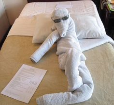 A funny and entertaining human shaped towel origami design. This is a good way to provide humor in your design and the shades adds to the comedic effect.