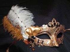 This is a beautiful and unique mask. Intricate gold fretwork is accented with bronze glitter filigree and clear, bronze, and champagne gemstones for added glam and sparkle. Features 2 ostrich plumes, ivory and gold, topped off with an asymmetrical satin and organza bow and a bronze dangly fan as the centerpiece.    Mask is attached to ribbons for ease in hands free wearing, perfect for the bride, bridesmaid or party girl. Wide variety of masks available in my store. Contact me for a custom…