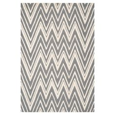 Stylishly anchor your living room or master suite with this lovely hand-tufted wool rug, showcasing an alluring chevron motif in dark grey and ivory.