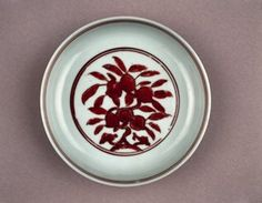 Porcelain saucer with rounded sides, straight rim, and tapering footring. Red overglaze enamel decoration. Peach tree with linzhi fungus within a double-circled roundel on inside centre. Four fruiting peach branches on exterior; petal band above the footring. Mark on base in red enamel. (Ming dynasty)