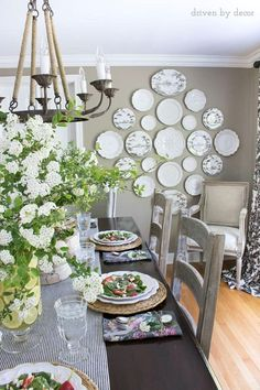 Gorgeous home tour! Love this black and white plate wall in gray dining room…