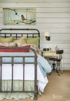 The vintage bed frame in a main house guest bedroom includes custom linens and a coverlet from Peacock Alley. The coordinating sconce is from Restoration Hardware.