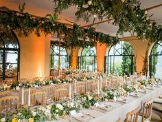 Greenery hangs overhead to create an indoor garden reception