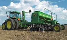JohnDeere tractor with a Box Drill attachment in a harvested corn field