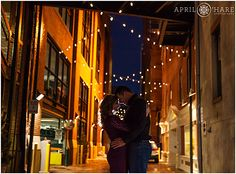 A pretty backlit dramatic night engagement photo in an alley in the Lodo neighborhood of Downtown Denver in Colorado. - April O'Hare Photography www.apriloharepho... #DowntownDenver #DenverEngagement #Denver #Colorado #ColoradoEngagement #LodoEngagement #DenverEngagementPhotos #DenverWeddingPhotographer #WinterEngagement #UrbanWedding #DenverUrbanEngagement #LarimerSquare #StringLights #LarimerSquareDenver #LarimerSquareEngagement #AlleyEngagementPhoto #NightEngagement
