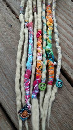 8 single ended wool dread extensions in lightest blonde, decorated with cotton tie dye wraps, embroidery floss, fimo tube beads, peace sign charms & a hippie sun charm