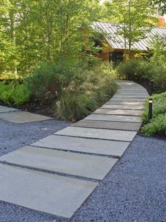 Monolithic ledge stone panels are set into the stone dust, as part of an award-winning residential landscape design project in Vermont by H. Keith Wagner Partnership. The walkway's arc lends privacy to the main house and a guest house on the estate.