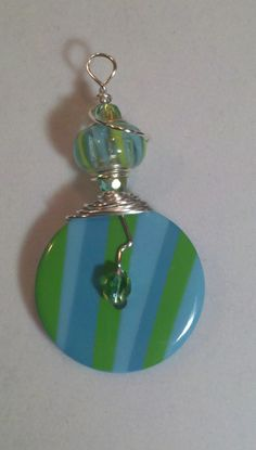 I wire wrapped sterling silver wire around a colorful glass bead ,and a matching button to make a unique pendant!