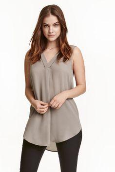 Blusa sem mangas em chiffon: Blusa sem mangas em crepe de chiffon com bordado ajour, decote em V e base arredondada.