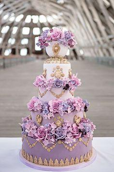 Un púrpura ombre Marie Antonieta pastel de bodas decorada con rosas grandes, querubines de oro y guirnaldas de oro.