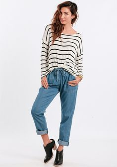 We love these slouchy light-washed denim pants  styled with an oversized top messy tucked into the front and paired with booties.