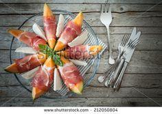 Overhead shot of plate with melon slices wrapped in prosciutto and mozzarella. - stock photo