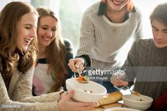 Stock-Foto : Four people sitting and standing at a table, a woman serving food into a bowl.