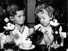 A famous Hollywood pair having a tea party with another famous Hollywood pair: Dickie Moore and Shirley Temple with Mickey and Minnie Mouse.