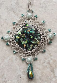 """Diamonds Diamonds       These were made with focal beads, from Fire Mountain Gems.  They were tatted with two strands of metallic sewing thread, using the Tatsmithing method of locking the bead in place with tatting in the front and back.  The pendents are 2"""" by 3""""."""