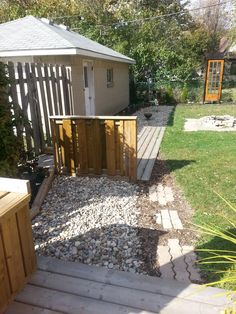 Off the main porch deck, is a mulch path with brick steps, a ground level decking area around the side entrance to the ground and an area beyond that with more river rock.