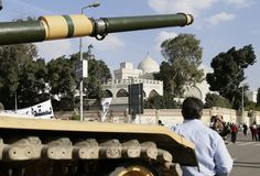 Egyptian army tank outside the presidential palace, background, in Cairo, Egypt, Saturday, Dec. 8, 2012. Egypt's military has warned of 'disastrous consequences' if the political crisis gripping the country is not resolved through dialogue. Open talks are the only way to overcome the nation's deepening conflict over a disputed draft constitution hurriedly adopted by Islamist allies of President Mohammed Morsi, and recent decrees granting himself near-absolute powers.(AP Photo/Hassan Ammar)