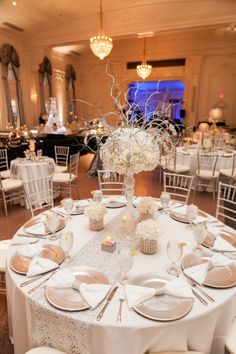 Gorgeous winter sparkly wedding centerpieces, in white and silver.  Hydrangea flowers with silver sparkle sticking out all around. Beautiful Gatsby inspired table runner adds to the elegance of the tables cape. Go to www.eb2events.com for more pics. #wedding #centerpieces #tablescape