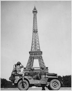 Soldados aliados observan cómo la bandera tricolor francesa es colocada en la torre durante la Liberación de París.