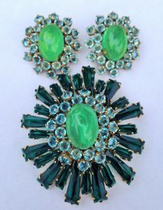 ITEM #13 STUNNER ALERT! This very large Schreiner ruffle brooch and earrings will stop you in your tracks! It measures well over 2.5 inches long, and domes up nearly 1.5 inches in profile. The earrings are equally large at 1.33 inches. It is rare to find the exact matching earrings, but here they are! The long tapered keystones are vivid emerald green. At the center of both the brooch and the earrings is a gorgeous flawed emerald art glass swirled cabochon that is surrounded by reverse set…