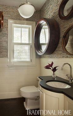 The mirrors in this powder room are made from reclaimed wood factory pullies. How cool is that? - Traditional Home ® / Photo: Eric Roth / Design: Daniel Reynolds