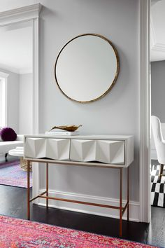 The entryway console, with its striking geometric qualities, pairs nicely with the simple mirror.