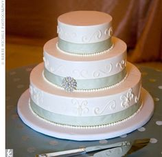 Ribbons in the same hue as the bridesmaids' sashes added a subtle splash of color to the ivory, buttercream-frosted cake. A pearl-and-diamond brooch, similar to the one on Danielle's gown, gave the dessert an elegant finish.