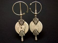 An old pair of Berber silver fibulae from the Anti Atlas in Southern Morocco made with two Spanish silver coins from the reign of Amadeo I (1871). They show incised decoration and an attractive patina due to intensive traditional use. Other names: -khul lala-,-khelâla-, -khelalât-. Early XXth century.