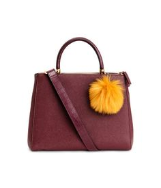 手提包 NT$ 1,699 粒面仿皮手提包,飾仿皮草絨球,單提把,側背帶可拆。三個夾層,其中兩個有拉鍊。11.5x22.5x29公分。