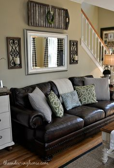 Decorating with a leather couch; Adding a mirror above the sofa is a great way to create the sense of space in a living room