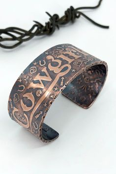 """Rustic Copper Cuffs - Limited edition Copper Reverse Roller Printed Cuffs with hand-finished detail. The """"Cowgirl Up"""" is on outside and a running horse design is on the inside. Heavy 12 gauge copper gives a rustic elegance to this piece. Because the """"plates"""" for these are hand cut with a jewelers saw only 1-3 impressions can be made. They are then hand finished with metal stamping on the edges, patina is applied and hand rubbed to a satin finish. Running Horses, Copper Cuff, Rustic Elegance, Graphic Patterns, Satin Finish, Metal Stamping, Handcrafted Jewelry, Cuff Bracelets, Silver Jewelry"""