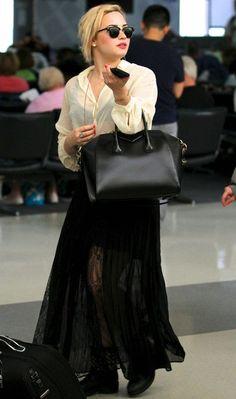 No aeroporto, Demi Lovato ficou boho-chic com saia longa transparente, camisa, coturno com tachas e óculos Ray Ban!