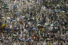2015 | CARNAVAL DE RIO DE JANEIRO, BRASIL - Spectators stand in plastic rain slickers as they watch the Viradouro samba school file past in the Carnival parade at the Sambadrome in Rio de Janeiro, Brazil, on February 15, 2015. The skies opened up Sunday evening, about an hour ahead of the start of the all-night-long extravaganza, drenching revelers and flooding streets near the Sambadrome.