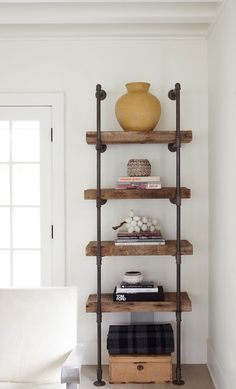 An industrial-style bookcase made of reclaimed wood and plumbing pipes adds warmth to the room's whitewashed color scheme.