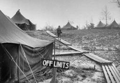 OFF LIMITS sign stuck in the mud next to wooden walkways where Amer. WACs tread their way between the tents in their camp during their tour of duty as switchboard operators & secretaries, on the Italian front in the Appennine Mountains. Italy, December 18, 1944 ~