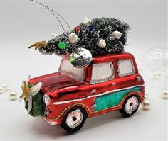 """Beach Christmas Christmas ornament red farm truck with a coastal twist! This new beach woody car is ADORABLE for your tree and will cause screams of joy when given as a gift to any beach lover!  It's a red old-fashioned glass red farm truck with a bottle-brush tree strapped to its roof. We add a real Florida bay starfish topper to the tree, and lots of tiny shells and teeny tiny miniature plastic lights to the tree.   Silver tone charm reads """"Not All Who Wander Are Lost"""". We love that…"""