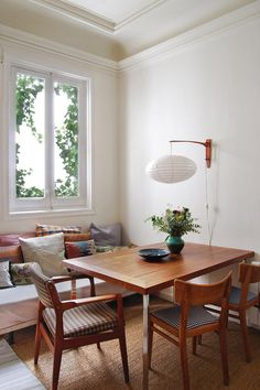 a bit bland but a wall sconce over the table in an apartment space is art and light at once - but you could have both