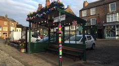 A bus shelter decorated with colourful knitted patterns