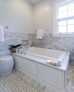 Built-in jacuzzi tub with marble tile wainscoting and custom tile floor